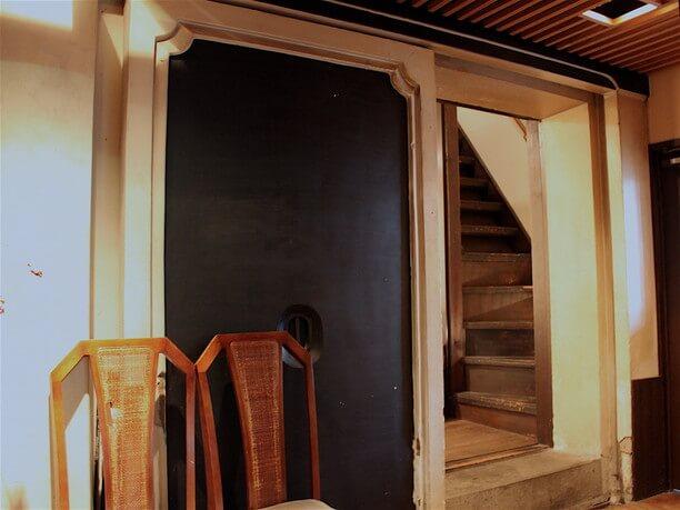 厚い扉の向こうにある木製の階段