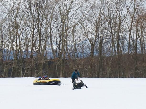 豪快なスピードで雪原を滑るスノーラフティング