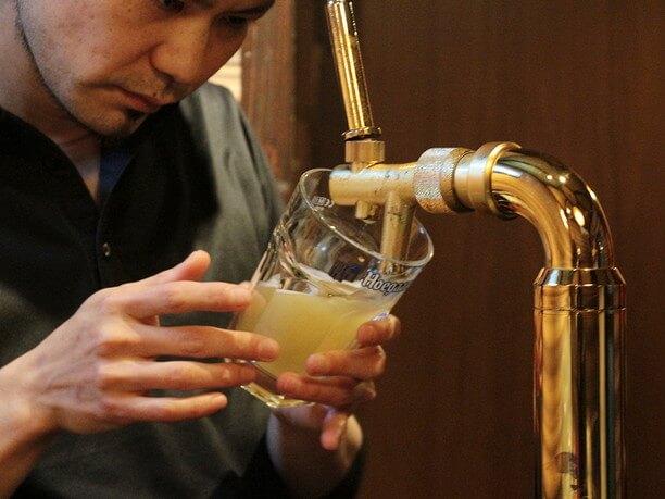 ビールサーバーからグラスに注いでいくオーナー