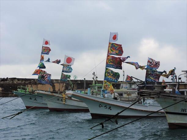 大漁旗を揚げていっせいに海へ向かう船